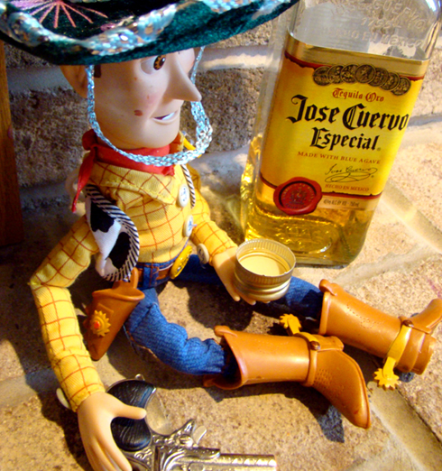 Woody drinking tequila and holding a pistol